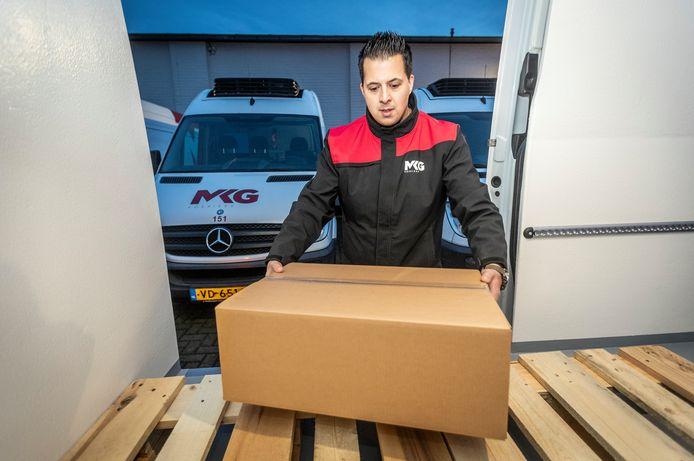 Chauffeur Brian van Goethem is bezig met het inladen van coronavaccins bij MKG Koeriers.