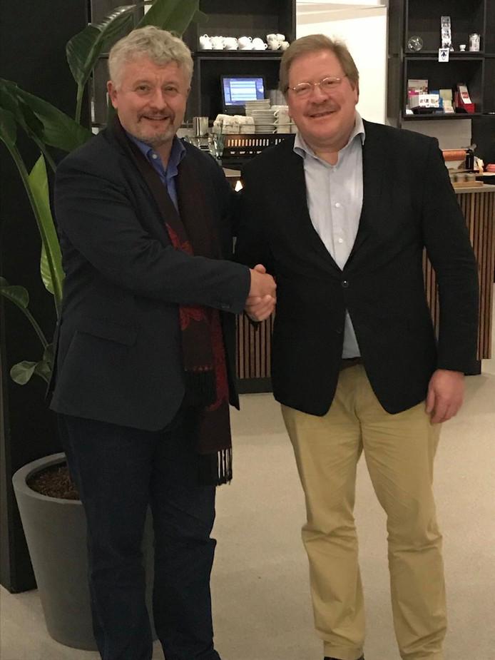 Sylvester Eijffinger (r) drukt de hand van Albert van der Wijk, de Moergestelnaar in het bestuur van Stichting Cultuurcentra Oisterwijk Moergestel (COM).