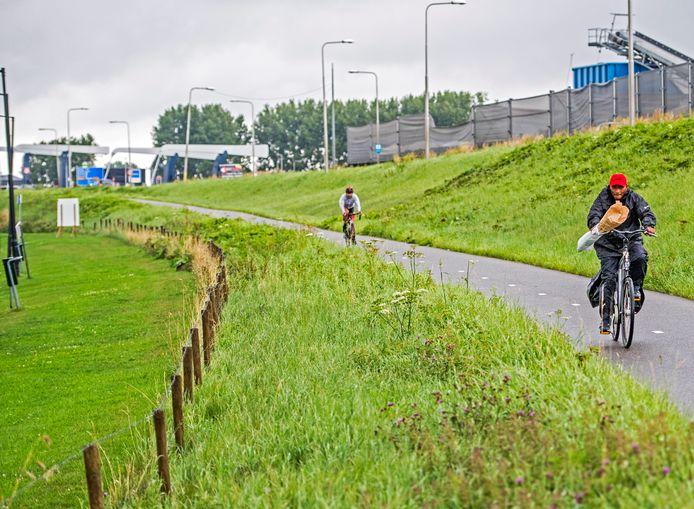 Fietsers tussen Gouda en Rotterdam fietsen langs de dijk tussen Gouda en Moordrecht.