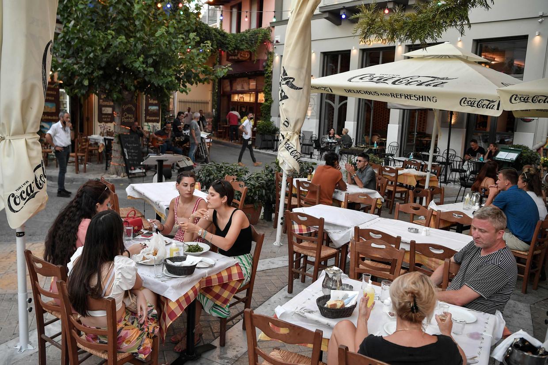Mensen op een terras in Athene. In Griekenland is binnen eten alleen nog mogelijk met een vaccinatiebewijs. Beeld AFP