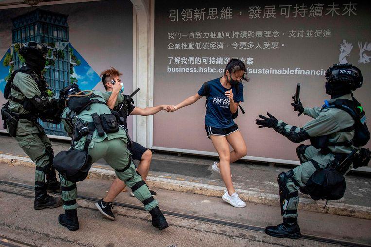 Twee demonstranten worden door de politie tegengehouden in Hongkong.