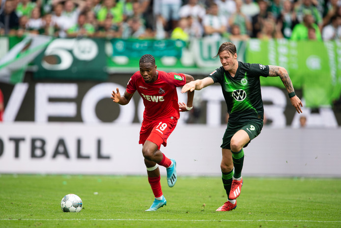 17 August 2019, Lower Saxony, Wolfsburg: Cologne's Kingsley Ehizibue (L) and Wolfsburg's Wout Weghorst battle for the ball during the German Bundesliga soccer match between VfL Wolfsburg and 1. FC Cologne at the Volkswagen Arena. Photo: Swen Pförtner/dpa - IMPORTANT NOTICE: DFL and DFB regulations prohibit any use of photographs as image sequences and/or quasi-video.