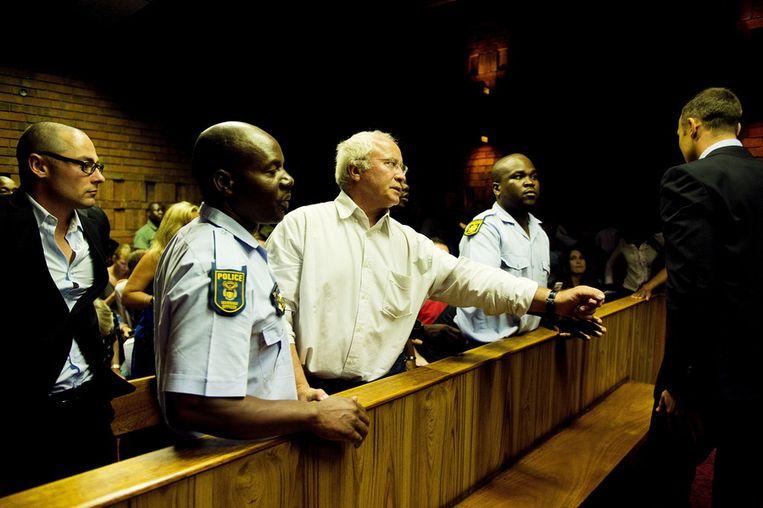 Henke Pistorius steekt een arm uit naar zijn zoon Oscar in de rechtbank. Beeld getty