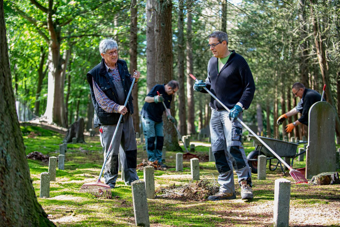 Vrijwilligers maken de begraafplaats op Vrederust schoon. Op de voorgrond Jos van Buijten (links) en Joost de Bont. Achter: Ton Bergs (links) en Bert Korteweg.