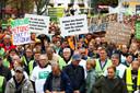 Actievoerende boeren dragen protestborden met teksten zoals (vlnr): 'Natuurbescherming met ons in plaats van tegen ons', 'Jullie zaaien niet, jullie oogsten niet maar weten desondanks alles beter', 'Ontneem je de boeren hun brood, dan ontstaat er snel grote nood'.