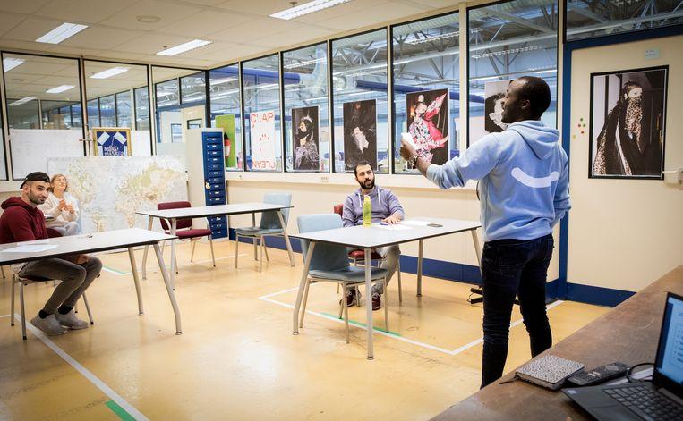 Medewerkers krijgen Nederlandse les in de fabriek. Beeld Negin Zendegani