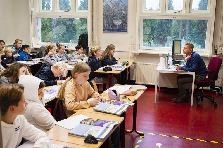 De ramen staan open voor ventilatie in een klaslokaal tijdens de les van het Amsterdams Lyceum.  Beeld ANP