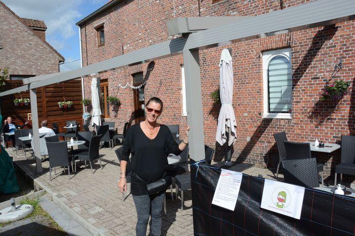 Uitbaatster Sonja bij de palen voor de overkapping van het terras. De rest van de constructie mag voorlopig niet geplaatst worden.