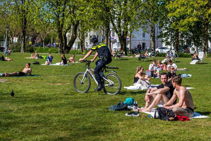 Zonaanbidders in Utrecht proberen afstand van elkaar te houden, agenten controleren naleving van de regels.