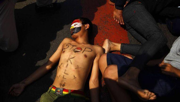 Een man in Jakarta, Indonesië, beeldt een dode Egyptenaar uit tijdens een solidariteitsdemonstratie in Jakarta. Beeld reuters