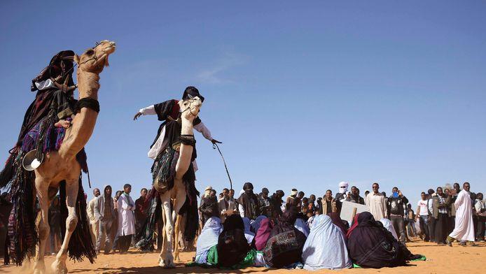 Toeareg-mannen demonstreren tijdens een cultureel festival in Ghat hun rijkunsten op kamelen.