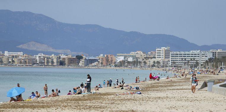 Toeristen op het strand van Playa de Palma in Palma de Mallorca, vlak voor Pasen. Beeld REUTERS