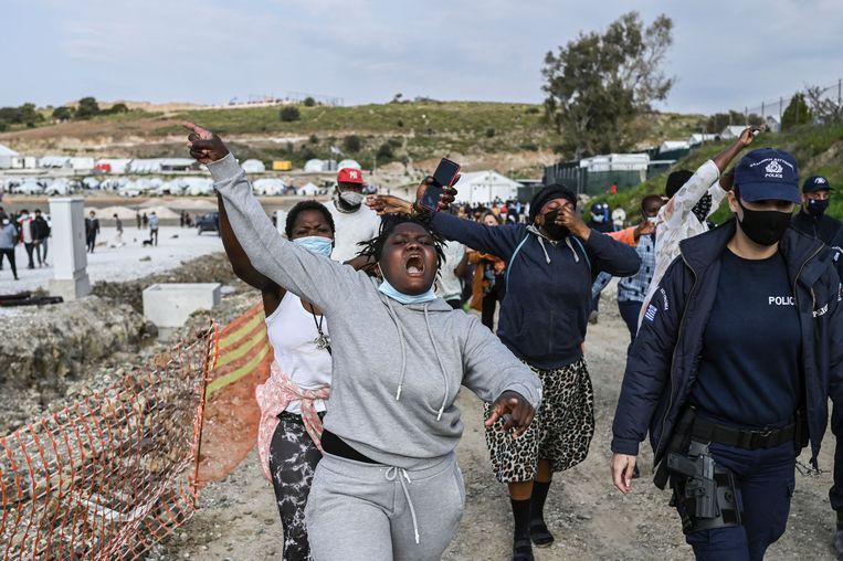 Afrikaanse vrouwen laten zich horen tijdens het bezoek van eurocommissaris Johansson aan hun kamp op Lesbos.  Beeld AFP