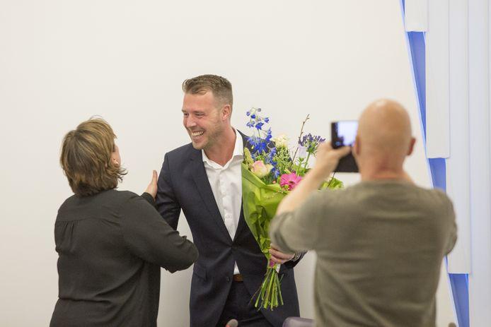 Maikel van der Neut wordt gefeliciteerd door D66-raadslid Jolanda Kuipers.