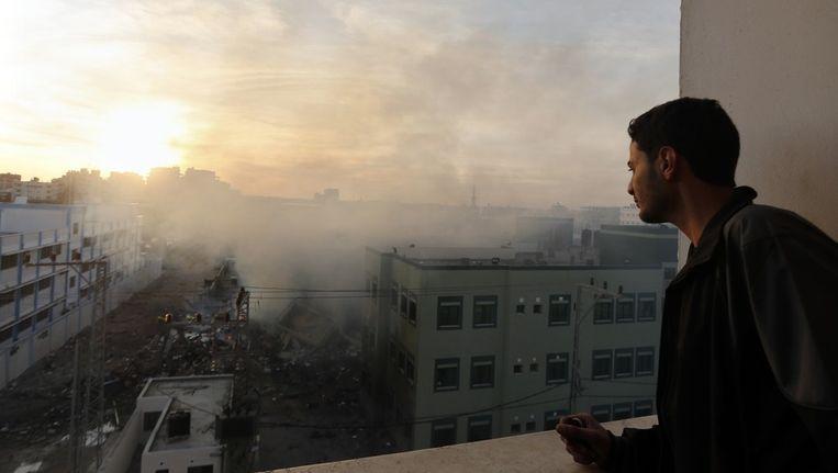 Een man kijkt uit op het ministerie van Binnenlandse Zaken van Hamas, dat werd geraakt door Israëlische aanvallen. Beeld reuters