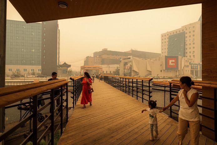 Des piétons marchent sur un pont alors que de la fumée provenant de feux de forêt proches plane au-dessus de la ville de Yakutsk, dans la république de Sakha, en Sibérie, le 27 juillet 2021.
