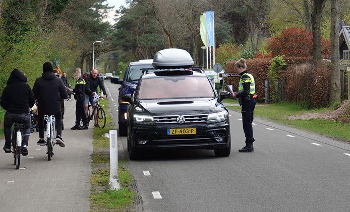 Agenten delen papiertjes uit met informatie die ze zoeken: een man die zich verdacht gedroeg op een camping bij Hardenberg, vorige week.