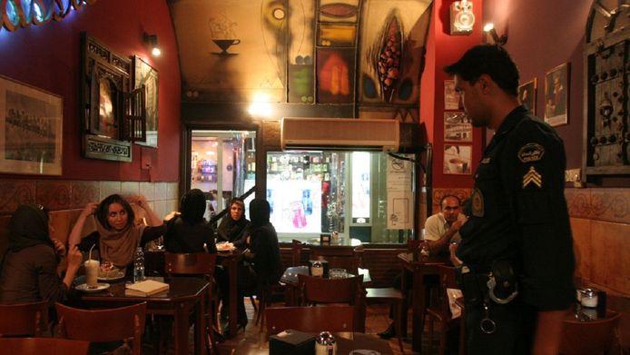 Een vrouw bedekt nog snel haar haar tijdens een politiecontrole in een restaurant in de Iraanse hoofdstad.