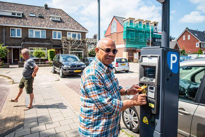Neville (r) koopt een kaartje bij de parkeerautomaat aan de Toussaintstraat. De kosten voor betaald parkeren in het centrum van Alphen zijn nog altijd een pijnpunt voor zowel de winkeliers als bezoekers.