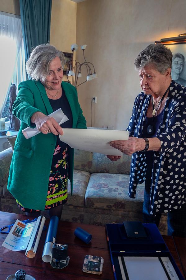 Minister Ank Bijleveld bekijkt samen met Ans Smolders de oorkonde horende bij de Koninklijke Onderscheiding, die de vrouw uit Bosschenhoofd in 2018 ten deel viel.