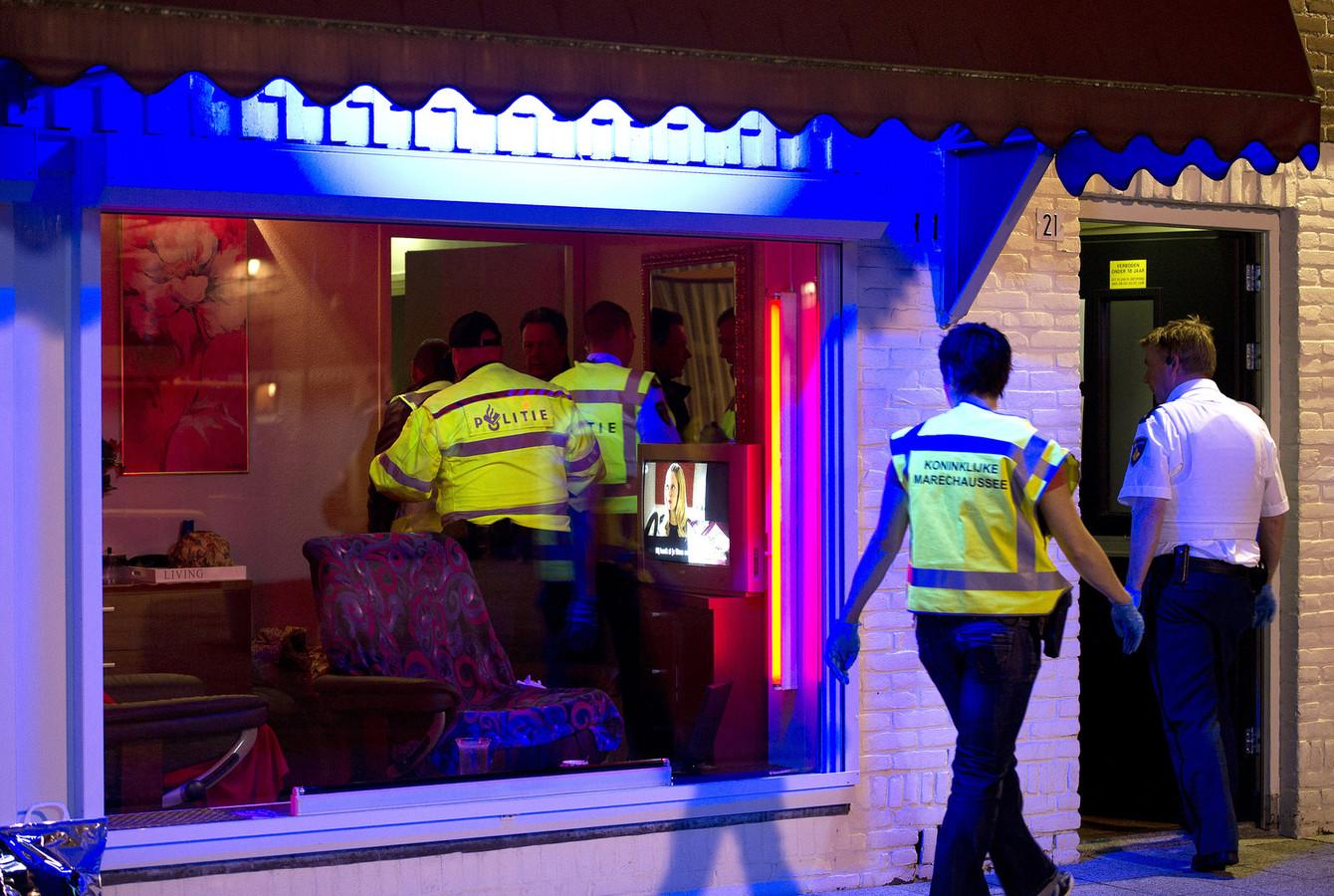 Politieagenten doorzoeken peeskamers op het Baekelandplein in Eindhoven tijdens een grote internationale actie tegen mensenhandel.