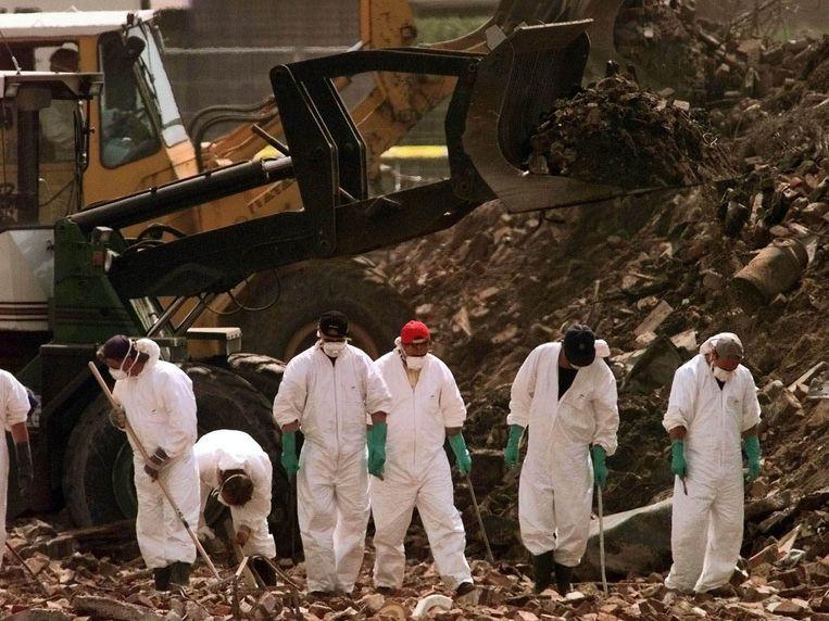 Een agenten van het RIT zoeken in het puin naar menselijke resten dinsdagmiddag 15 mei.  Beeld GPD/VINCENT JANNINK