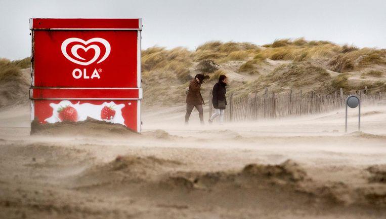 Bezoekers lopen door de storm op het strand van IJmuiden. Beeld anp