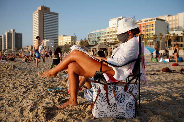 Een vrouw op het strand van Tel Aviv, met een mondkapje op. Beeld Reuters