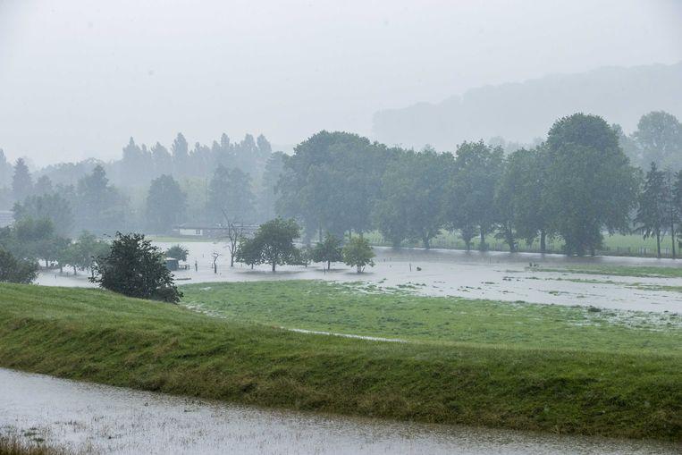 Het water in de Geul bij Wijlre loopt over de oever, aan het begin van de grote overstromingen. Beeld ANP
