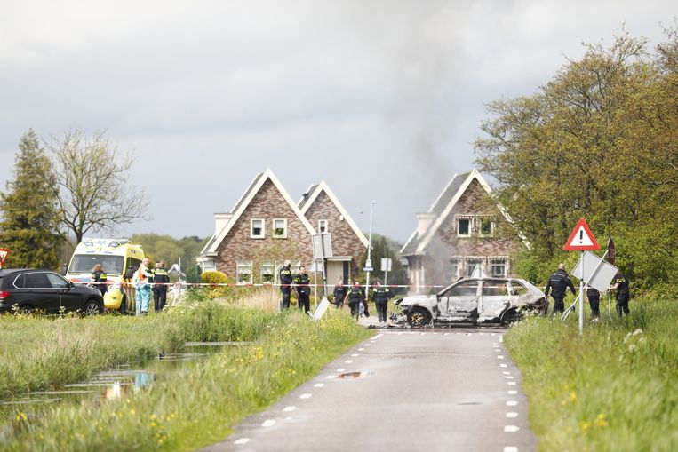 Hulpdiensten bij een uitgebrande vluchtauto.  Beeld ANP