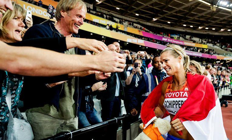 Een emotionele Dafne Schippers wordt gefeliciteerd door haar ouders en broer na de finale van de 200 meter hardlopen op het WK atletiek in het Olympisch Stadion in Londen. Beeld ANP