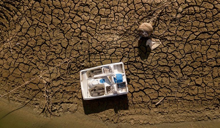 Een gestrande boot ligt op 5 september 2021 op een droog deel van de meerbodem van Lake Oroville in Oroville, Californië. - Lake Oroville heeft momenteel 23% van zijn capaciteit en lijdt onder extreme droogte. Beeld AFP