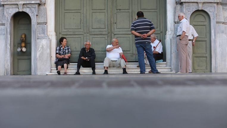 Gepensioneerden wachten voor de deuren van de Nationale Bank in Athene tot ze hun pensioen kunnen ophalen. Beeld GETTY