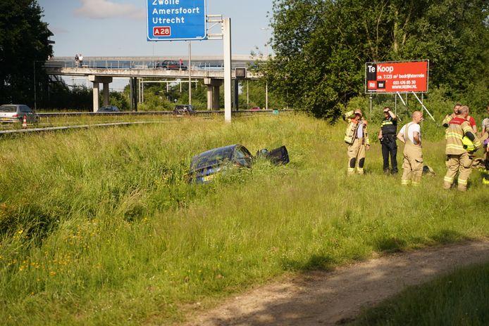 Brandweerlieden bij de deels te water geraakte Tesla langs de A1.
