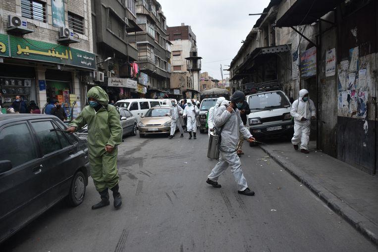 Syrische gemeentewerknemers steriliseren de straten van Damascus om verdere verspreiding van Covid-19 te voorkomen. Beeld Hollandse Hoogte / EPA