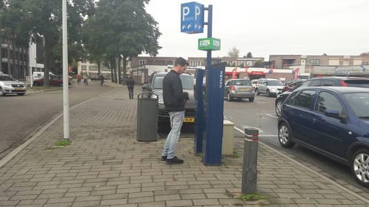 Een automobilist leest het briefje op de parkeerautomaat op de Dr. Bardetplaats.