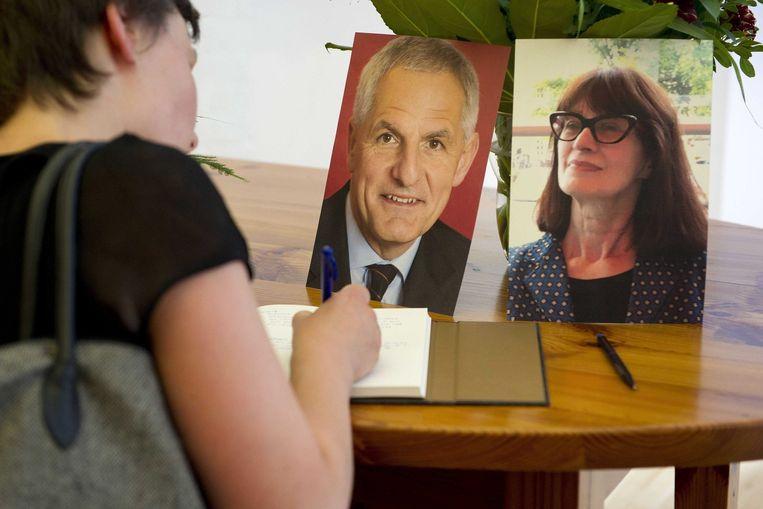 Joep Lange en Jacqueline van Tongeren op foto's bij een condoleanceregister in het AMC in Amsterdam. Beeld epa