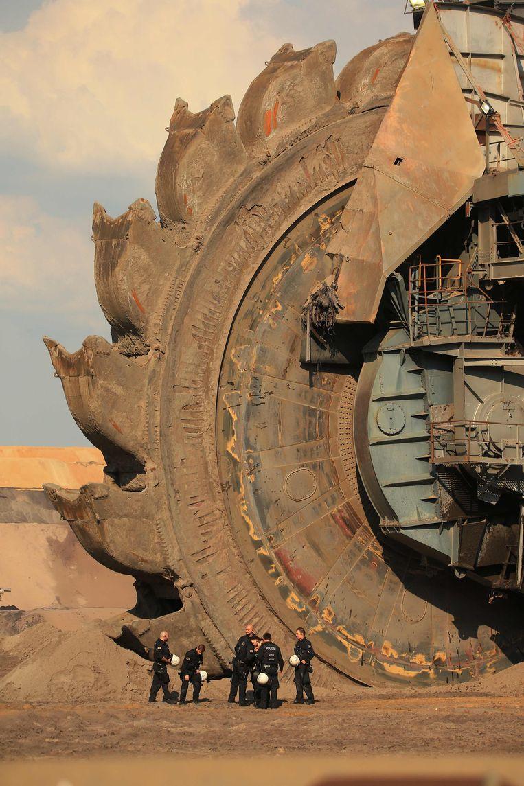 Agenten beschermen een onderdeel van de mijnwerkinstallatie tegen klimaatactivisten die protesteren in de bruinkoolmijn in Garzweiler in Duitsland.  Beeld AFP