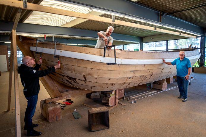 De bouw van de historische trekschuit Den Eerste Snik ligt op schema: het casco van de boot is klaar. Vrijwilligers Wim (links) en René zijn hard aan het werk. Frank Baart, voorzitter van de stichting Zorg en Vlijt, kijkt trots toe.