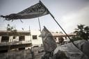 Een islamitische vlag wappert bij een checkpoint in Aleppo
