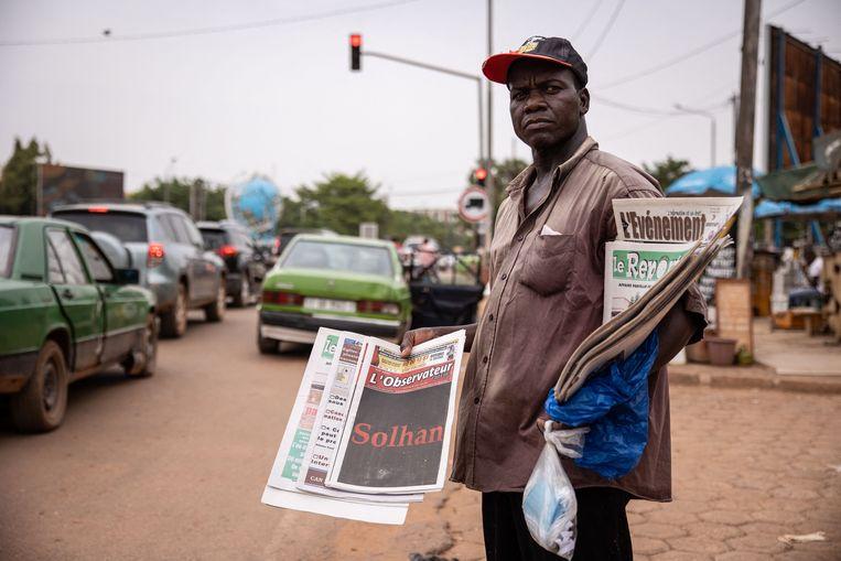 Een krantenverkoper in Burkina Faso met een exemplaar van L'Observateur Paalga, een lokaal dagblad. Op de voorpagina staat alleen de naam van het dorp waar moslimextremisten begin juni 160 mensen, onder wie zeker 20 kinderen, hebben vermoord.  Beeld AFP
