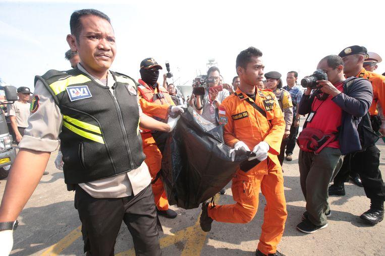 ► Reddingswerkers dragen een slachtoffer van de vliegramp weg in de haven van Tanjung Priok. Beeld EPA
