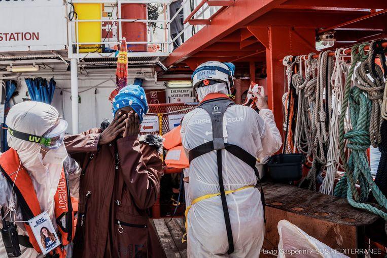 Een van de 236 migranten die van de rubberboot werden gered door hulporganisatie SOS Méditerranée. Beeld EPA