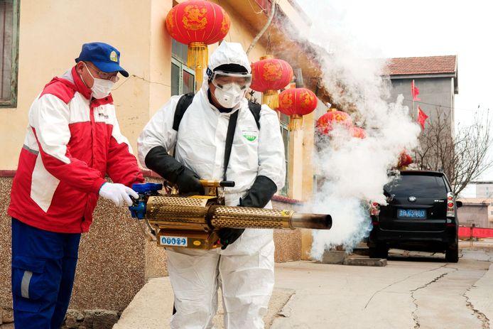 Een man in beschermende kledij desinfecteert een straat in China in aanloop naar de nieuwjaarsfeesten.