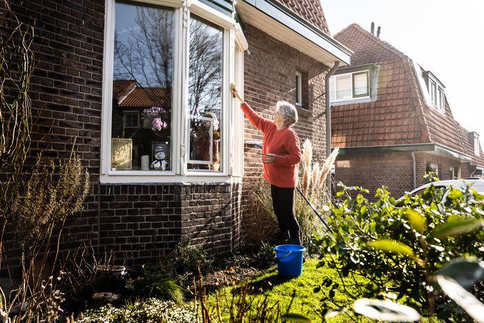 Lente in Arnhem op de Geitenkamp: Hannie van de Weerd is de ramen aan het schoonmaken.