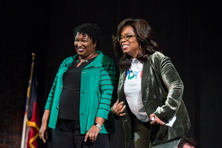 Abrams en Oprah Winfrey donderdag tijdens een verkiezingsbijeenkomst in Marietta in de staat Georgia.  Beeld Getty Images