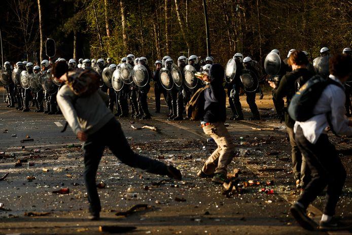 Mensen gooien stenen en flessen richting de politie aan het Ter Kamerenbos.