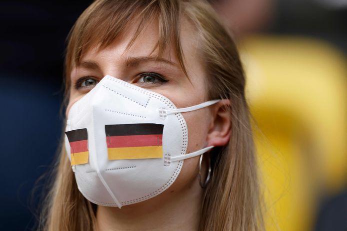 Een Duitse voetbalfan voorzien van mondkapje.