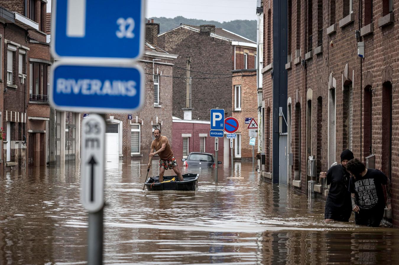 Sur cette photo d'archive du 16 juillet 2021, un homme fait avancer un bateau dans une rue résidentielle après une inondation à Angleur, dans la province de Liège, en Belgique.