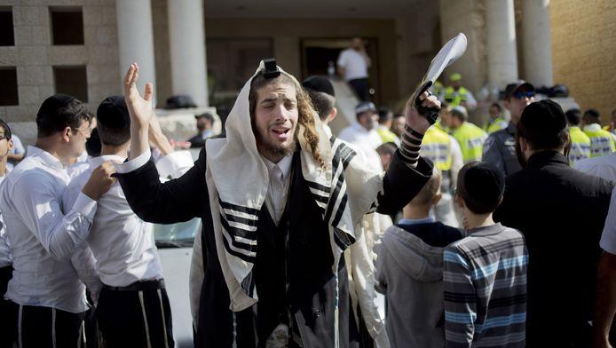 Een orthodoxe jood bidt terwijl achter hem de plaats van de aanslag wordt opgeruimd.